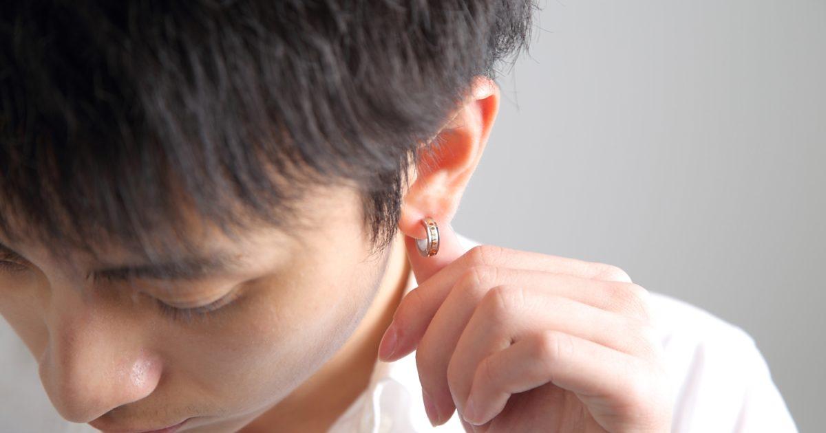 片耳にイヤリングを着用している男性